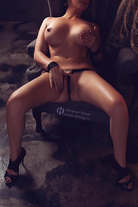 Женщина с большой грудью трогает себя за киску на эротической фотосессии