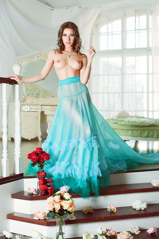 Девушка в нежно мятном платье спускается по лестнице с обнаженной грудью
