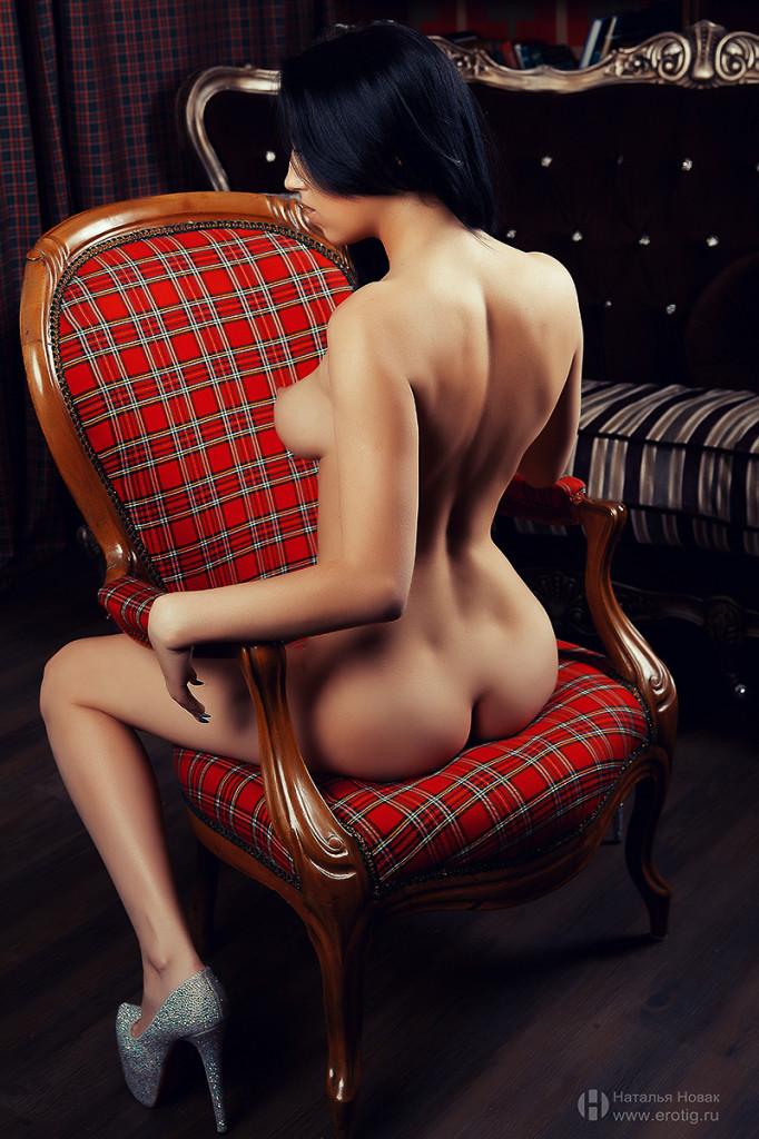 Брюнетка на красном кресле во время эротической фотосессии