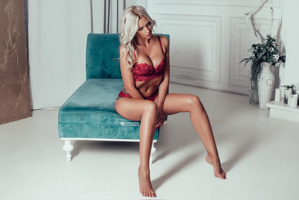 Блондинка в красном белье на эротической фотосессии в Европе сидит на голубом кресле
