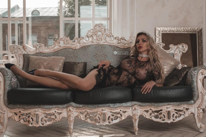 Сексуальная женщина на откровенной будуарной фотосессии в стиле ню лежит на диване в прозрачном пеньюаре в ожидании своего мужа