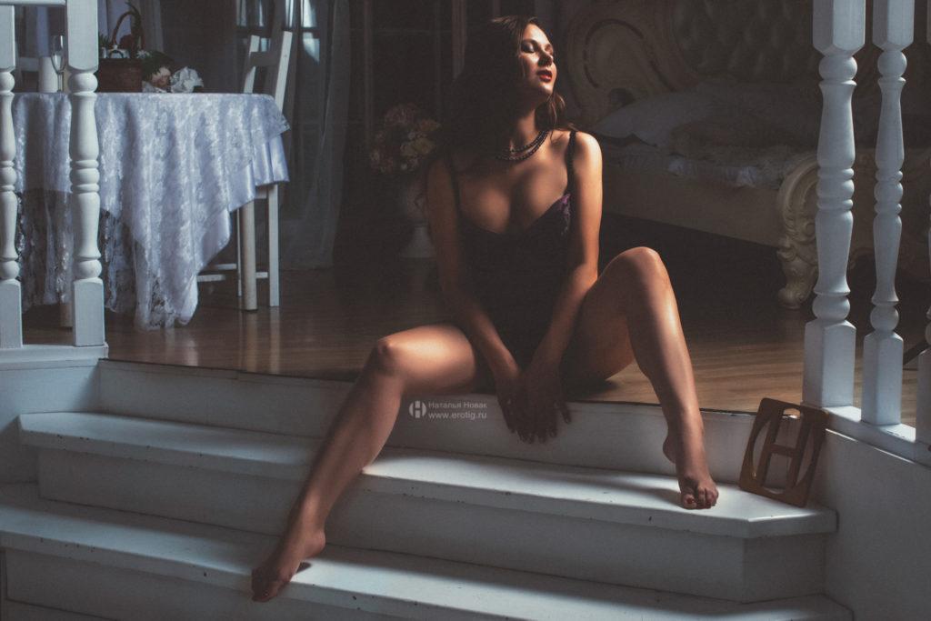Девушка с большой грудью сидит на лестнице на ню фотосессии