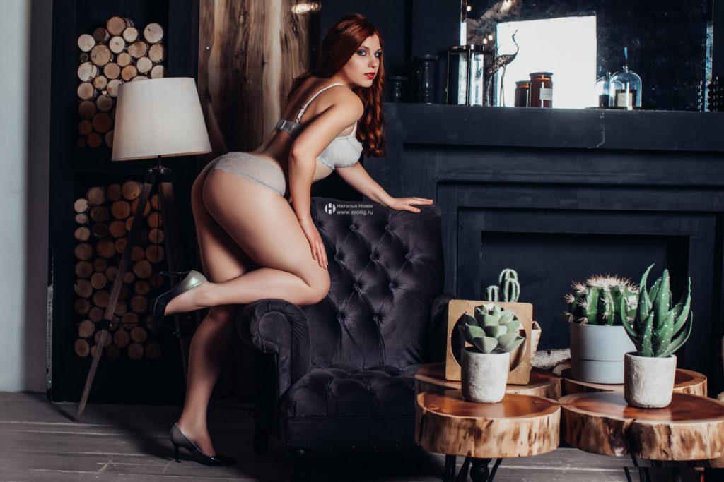 Эротическая фотосессия в стиле Будуар ню у женского фотографа Натальи Новак. Рыжая женщина позирует в нижнем белье около кресла глядя в камеру в полный рост